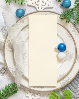 Silver and blue festive table setting with ornaments and fir tree branches with blank card template