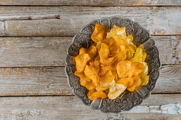 Silver bowl of mixed potato chips on wood