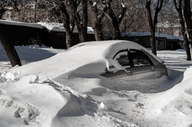 Silver car is in the parking lot in a big snow bank. weather problems
