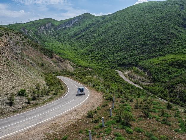 山の曲がりくねった上の銀色の車。森に覆われた急な山の斜面。緑の惑星。
