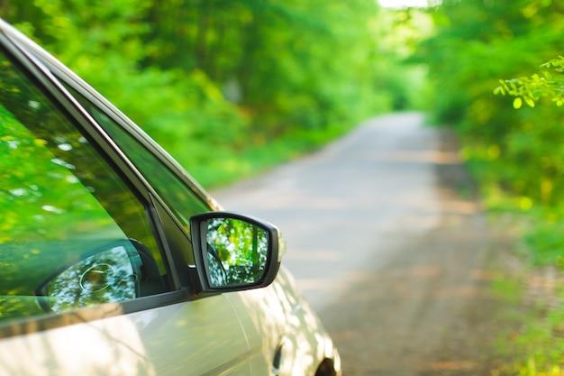森の中の道の道端に立っている銀色の車。側面図