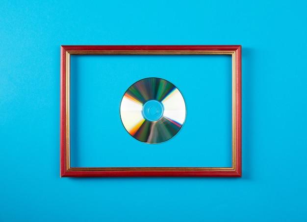 Серебряный диск в деревянной фоторамке на синей стене. символическая награда.