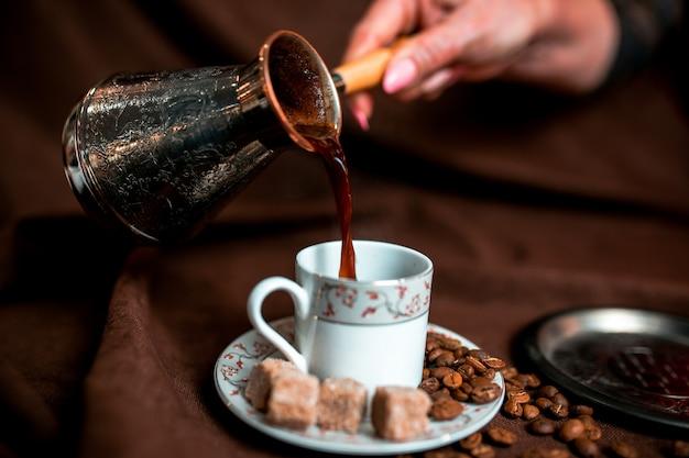 ダークブラウンのテキスタイルに銀のcezveとコーヒー豆。