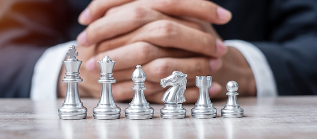 Silver chess figure team (king, queen, bishop, knight, rook and pawn) with businessman manager strategy, success, management, business planning, tactic, thinking, vision and leader concept