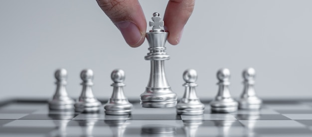 Silver chess king figure stand out from the crowd on chessboard background.