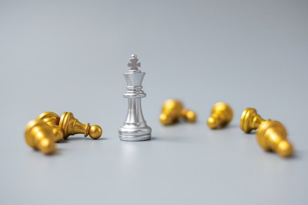 Silver chess king figure stand out from crowd of enermy
