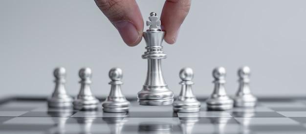 Фигура серебряного шахматного короля выделитесь из толпы на фоне шахматной доски.