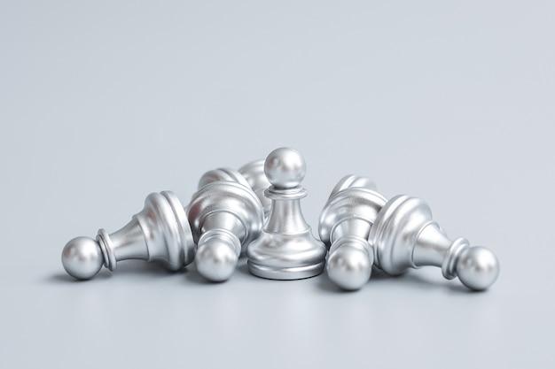 Серебряная пешечная фигура в шахматах выделяется из толпы противников или противников. стратегия, успех, менеджмент, бизнес-планирование, подрыв, победа и концепция лидерства