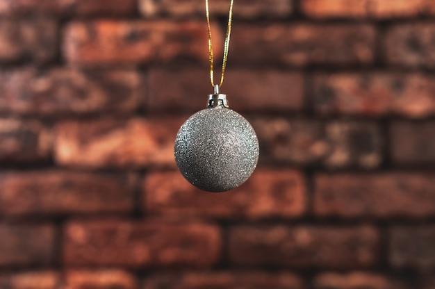 赤レンガの壁の背景にシルバーのクリスマスボール