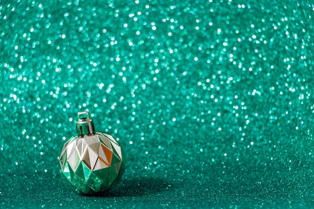 Silver christmas ball on shiny green background. new year concept, color tidewater green.