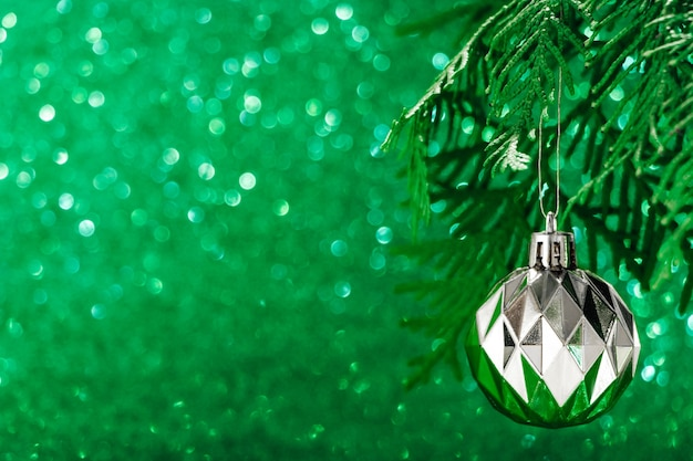Silver christmas ball on shiny green background. new year concept, place for text.