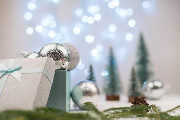 Серебряные елочные шары в подарочной коробке на фоне елок и синего боке.
