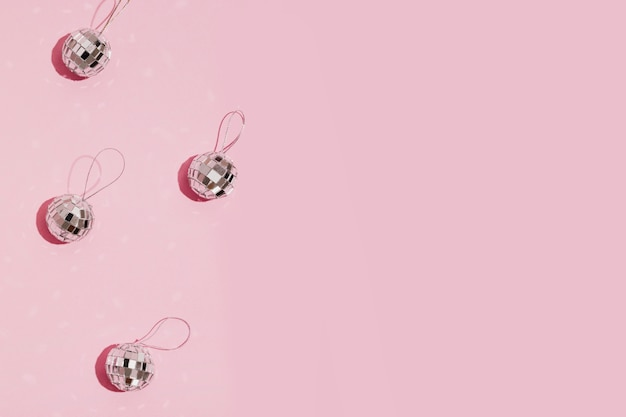 Silver christmas balls on pink background with copy space
