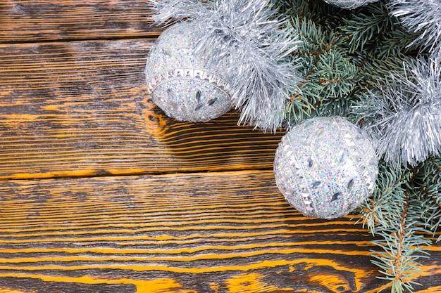 あなたの季節の挨拶のためのコピースペースで素朴な木の背景の上に輝く見掛け倒しでシルバーのクリスマス安物の宝石のコーナーの装飾