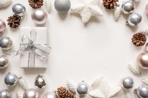 Серебряные елочные игрушки шары и подарок на белом