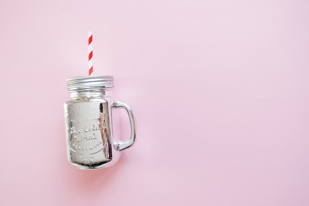 Silver christmas mason jar with straw on pink background. winter christmas flat lay