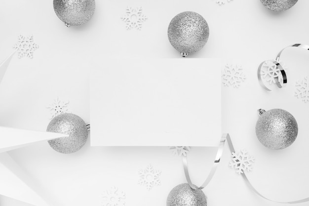 Silver christmas ornaments on white table