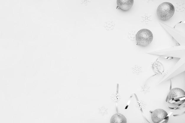 Ornamenti d'argento di natale sulla tavola bianca