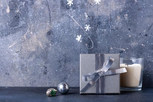シルバーのクリスマスのおもちゃ、テキストの灰色の背景の場所にギフトが入った箱
