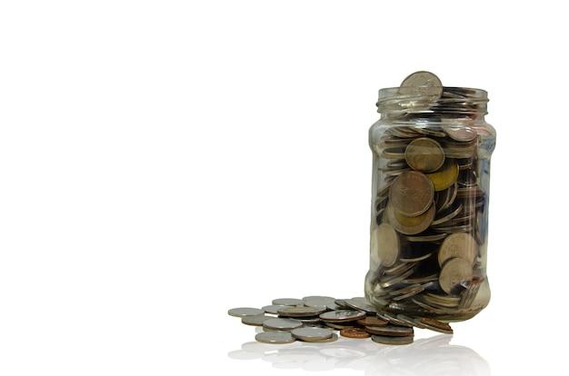 Серебряные монеты в стеклянной банке. понятие финансов и экономии денег