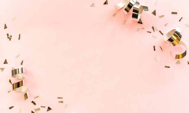 Серебряный цвет катящейся ленты и конфетти на розовом фоне с копией пространства