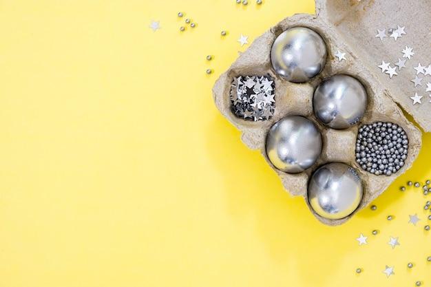 黄色のテクスチャ背景の卵ボックスに銀色のイースターエッグと星