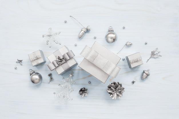 シルバー色のギフトボックスと水色のテーブルの上のクリスマスの装飾