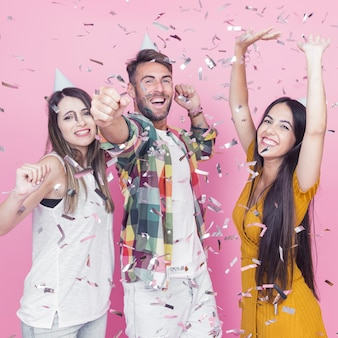 Silver confetti falling over the friends dancing against pink background