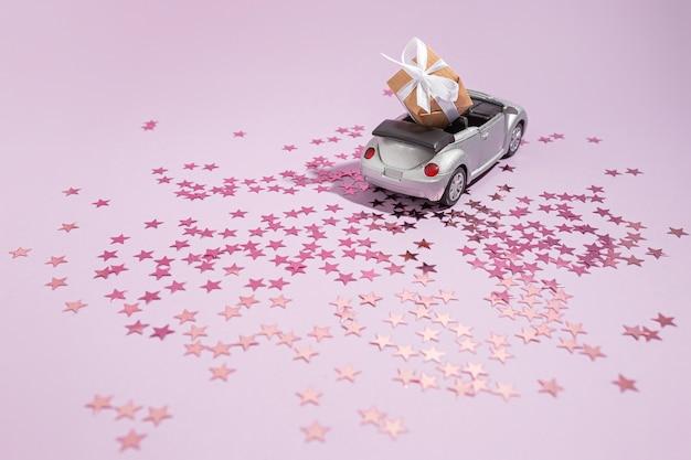 보라색 배경에 휴가 선물을 들고 은색 컨버터블 자동차. 새 해, 크리스마스와 발렌타인 개념