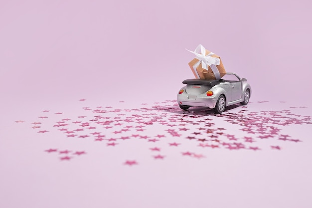 Silver convertible car carrying a gift for the holiday on a purple background. new year, christmas and valentine concept