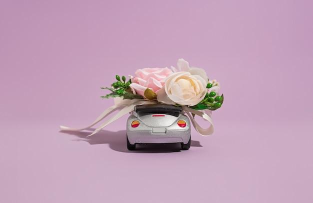 Серебряная модель кабриолета с цветами на фиолетовом фоне. концепция доставки цветов и подарков к празднику и торжеству