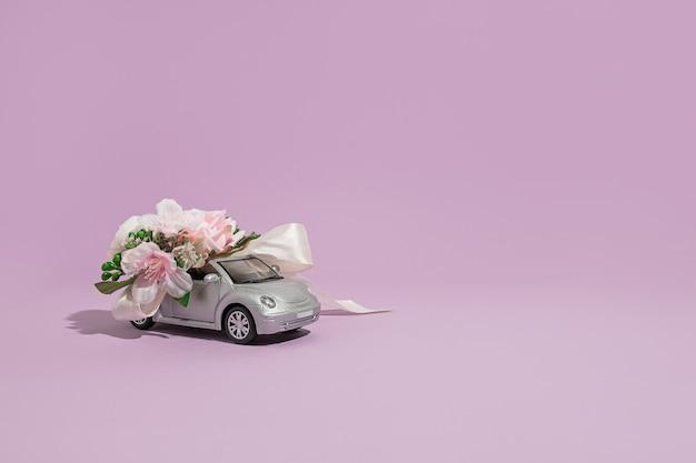 보라색 배경에 꽃이 있는 은색 컨버터블 소형 자동차 모델. 휴일 및 축하를 위한 꽃과 선물 배달의 개념