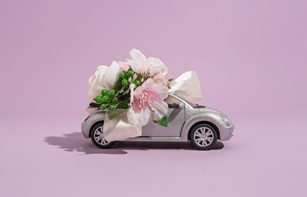 Silver convertible small car model with flowers on a purple background. the concept of delivery of flowers and gifts for the holiday and celebration