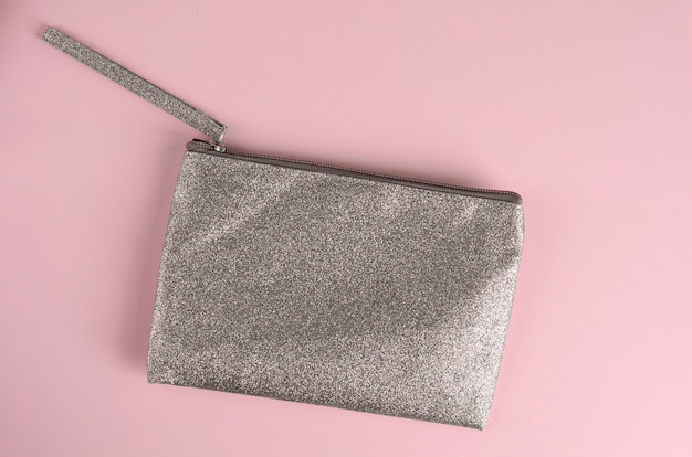 Silver cosmetic bag on pastel pink
