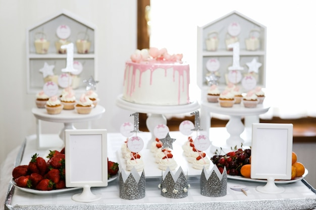 Silver crowns stand on the table with pink bakeru and berries
