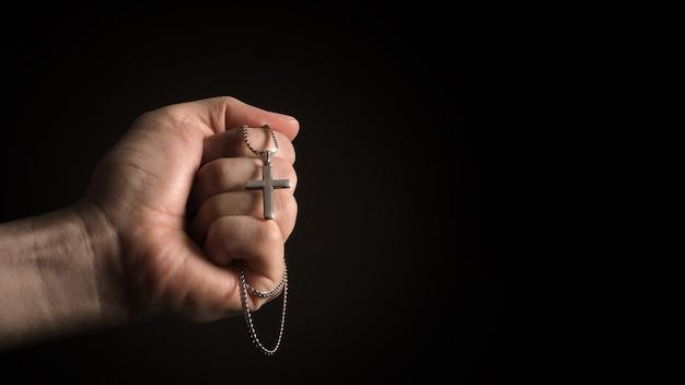 Серебряное распятие или крест кулон и ожерелье на теле или руке студия выстрел черный цвет фона