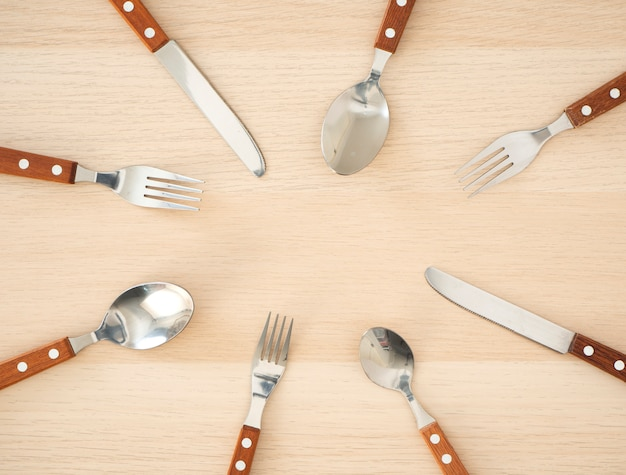 Silver cutlery set on wooden table