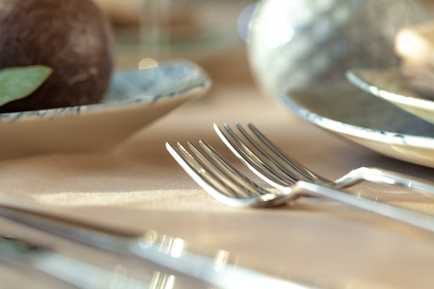 Silver cutlery on table top with tablecloth