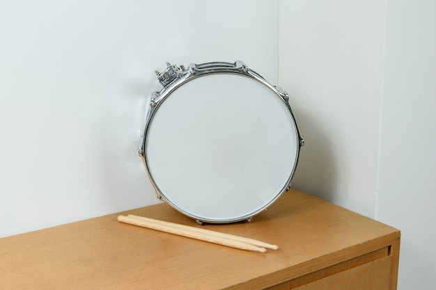 Silver drum with drumsticks