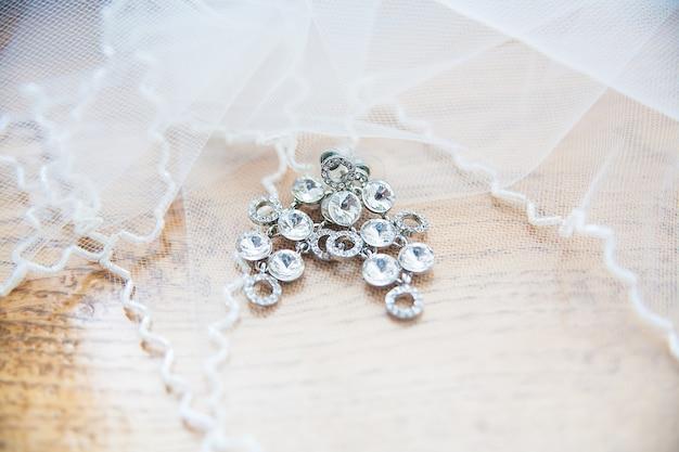 Серебряные серьги невесты крупным планом лежат на вуали