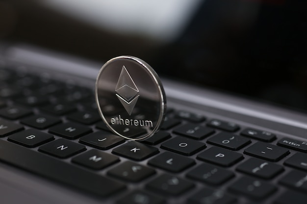 Silver ethereum coin is lying on laptop