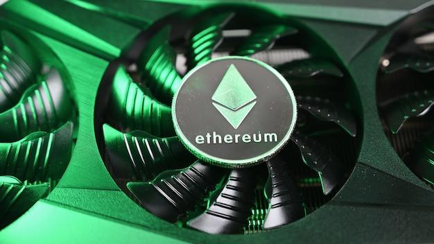 이더리움 은화는 녹색 불빛이 비추는 검은색 비디오 카드에 놓여 있습니다. 암호화폐.