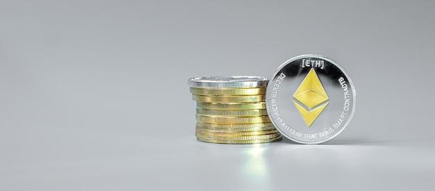 Стопка серебряных монет эфириума на сером фоне