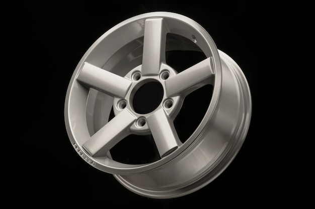 Серебряный пятиспицевый обод легкосплавных дисков для кроссовера или внедорожника на черном фоне.
