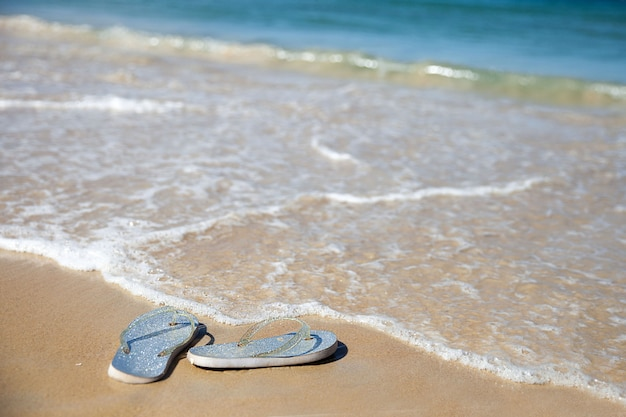 波の近くの砂浜でシルバーのビーチサンダル