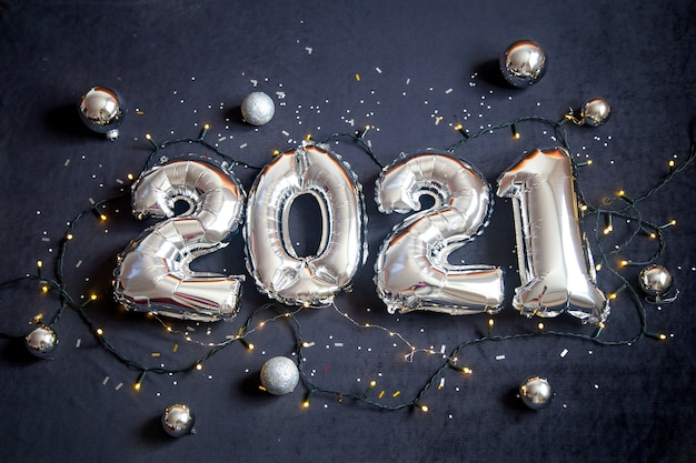 Silver foil balloons made new years number on black background with garland and balls.