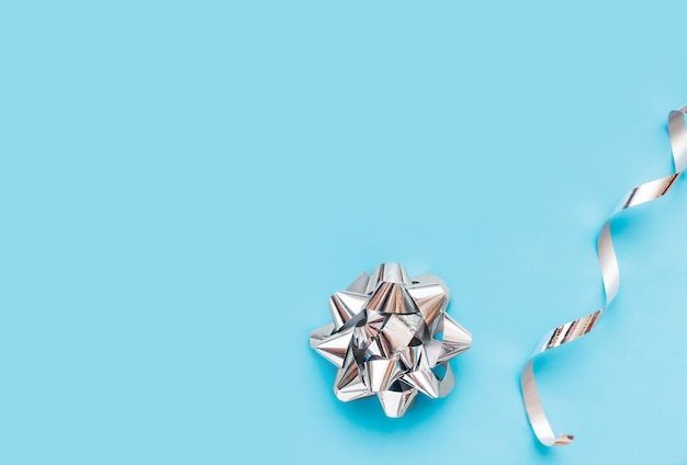 Silver foil bow and packing silver ribbon on blue background