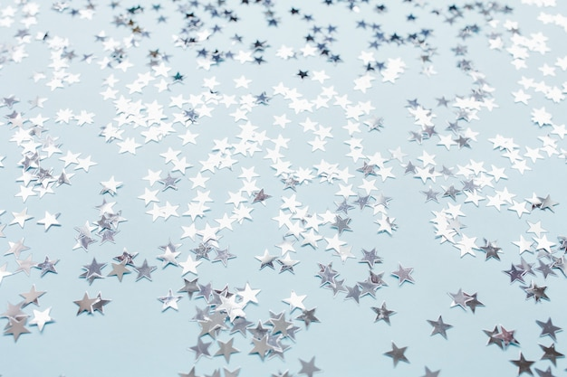 青い背景の上の銀箔紙吹雪星