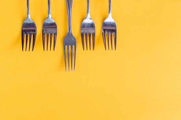 Silver forks on bright yellow background with copyspace. flat lay