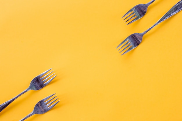 Silver forks on  yellow background